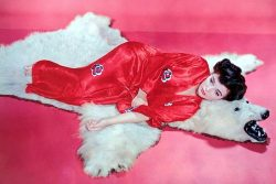 Joan Collins barefoot in silk kimono on bear skin rug